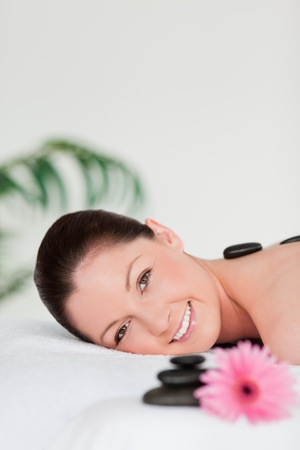 Portrait of a young woman with massage stones and a pink gerbera photo