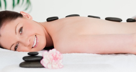 Red-haired woman receiving a hot stone massage photo