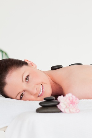 Portrait of a red-haired woman receiving a hot stone massage photo