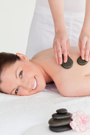 Smiling young redhead woman having a hot stone massage photo