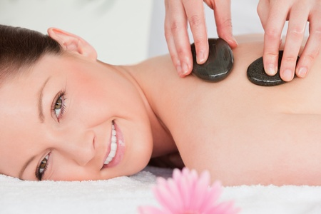 Young woman looking at the camera while having a hot stone massage Stock Photo - 10074129