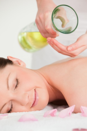 Portrait of a happy woman having massage oil versed on her back photo