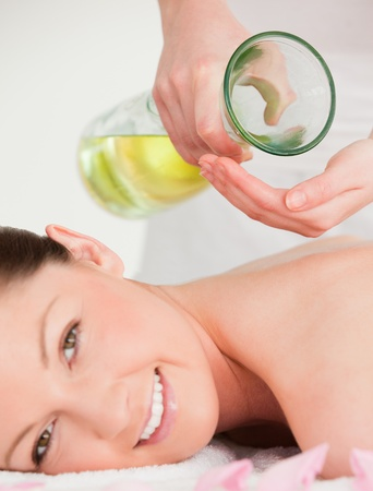 massage oil: Portrait of a smilling woman getting massage oil on her back in a spa