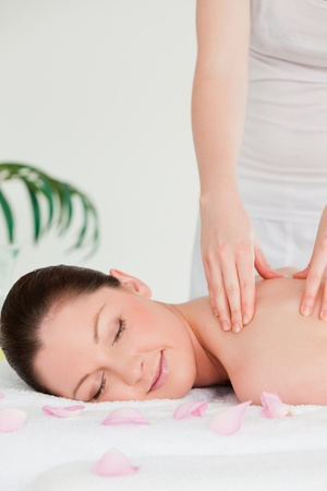 Portrait of a young woman closing her eyes during a massage photo