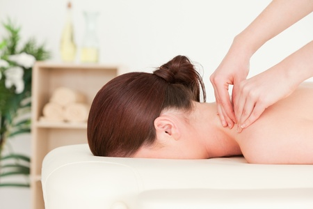 Red-haired woman receiving a back massage photo