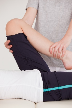 Portrait of a masseuse stretching the leg of a youn woman photo