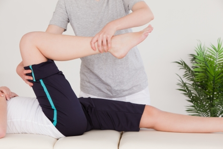 male massage: Masseuse stretching the right leg of a young woman Stock Photo