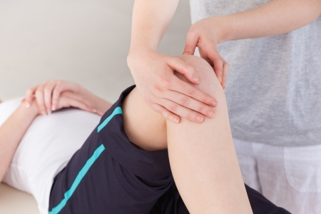 physiotherapist: Masseuse massing the knee of a sportswoman