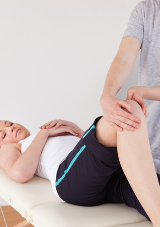 Portrait of a masseuse massing the knee of a young woman photo