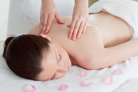 Cute redhead woman having a back massage surrounded by petals photo