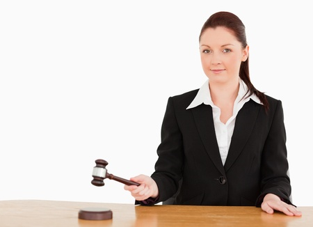 appraise: Young judge knocking a gavel smiling at the camera  against a white background