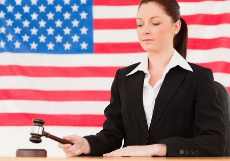 Serious young judge knocking a gavel with an American flag in the background photo