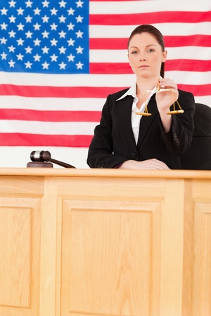 Cute judge holding scales of justice with an American flag in the background Stock Photo - 10074133
