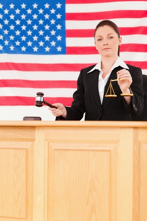 Young judge knocking a gavel and holding scales of justice with an American flag in the background photo