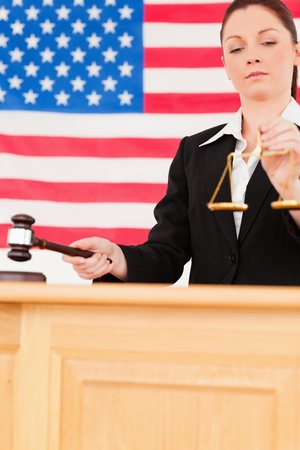 Portrait of a cute judge knocking a gavel and holding scales of justice with an American flag in the background photo