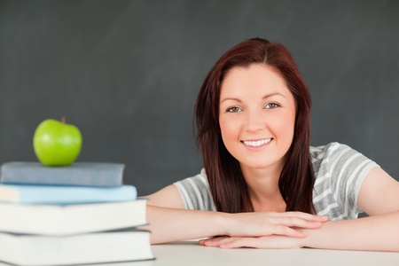 Close up of a student with books and an apple in a classroom photo