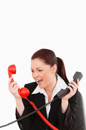 Beautiful secretary driven crazy by the phone calls against a white background photo