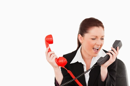 Cute secretary driven crazy by the phone calls against a white background photo