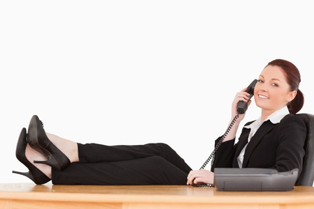 Good looking businesswoman on the phone in her office against a white background photo
