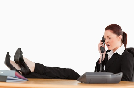 Unhappy business woman on the phone in her office against a white background photo