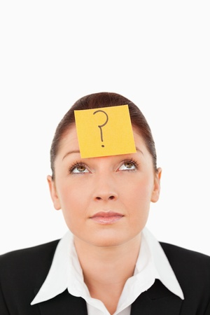 Cute businesswoman with a question tag on her forehead against a white background photo