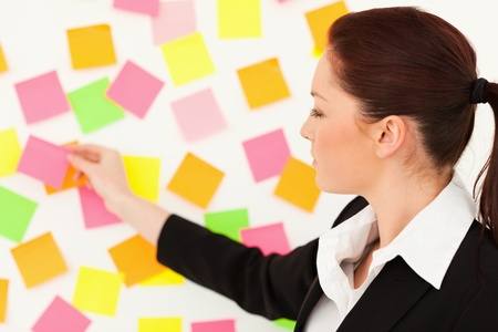 Young woman putting repositionable notes on a white wall photo