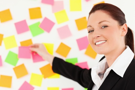Cute woman putting repositionable notes on a white wall photo