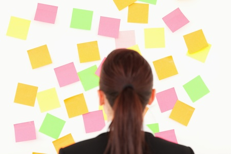 Red-haired woman looking at a wall full of repositional notes on a white wall Stock Photo - 10069704
