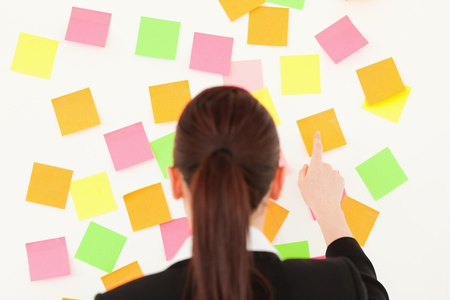 Red-haired woman taking a repositional notes on a white wall photo
