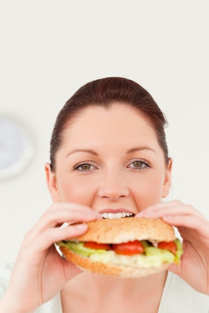 Gorgeous woman eating a sandwich for lunch in her kitchen photo