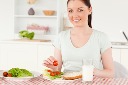 Attractive woman ready to eat a sandwich for lunch in her kitchen photo