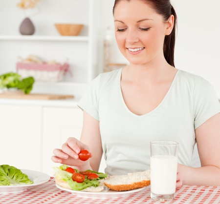 Charming woman ready to eat a sandwich for lunch in her kitchen photo
