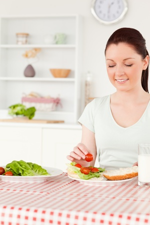 Cute woman ready to eat a sandwich for lunch in her kitchen photo