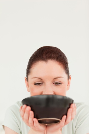 Pretty woman posing while holding a bowl in her kitchen photo