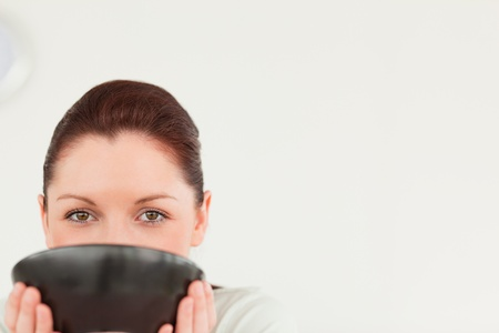 Charming female posing while holding a bowl in her kitchen photo