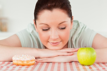 Good looking woman posing with a donut and a green apple in the kitchen photo