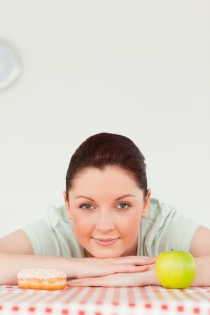 Pretty woman posing with a donut and a green apple in the kitchen photo