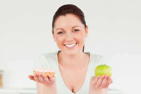 Good looking woman posing while holding a donut and a green apple against a white background photo