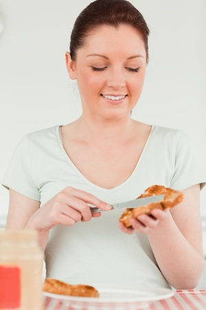 Cute woman preparing a slice of bread and marmalade in the kitchen photo
