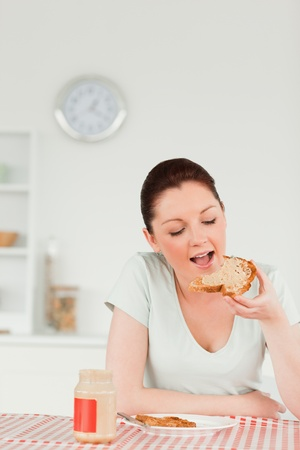 Beautiful female preparing a slice of bread and marmalade in the kitchen photo