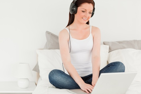 Gorgeous woman relaxing with her laptop in her bedroom Stock Photo - 10070818