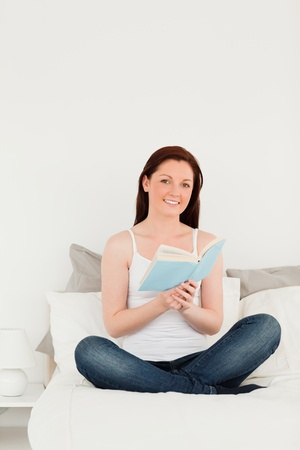 Gorgeous female reading a book while sitting on her bed photo