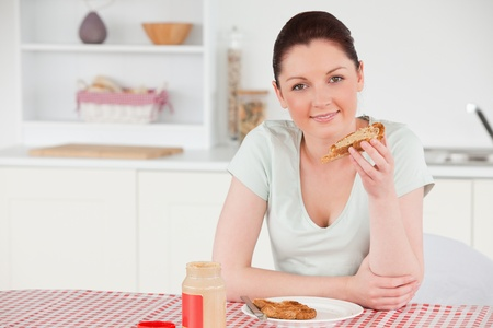 Beautiful woman posing while eating a slice of bread in her kitchen photo