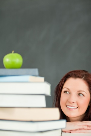 Portrait of a young student looking at the apple on the top of her books in a classroom photo