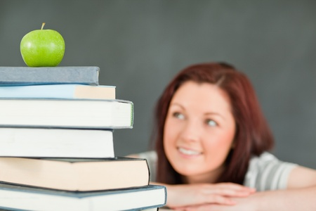 Young female student with a stack of books in a classroom Stock Photo - 10074280