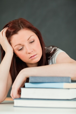Young student fallling asleep with her forearm on her books in a classroom Stock Photo - 10074399