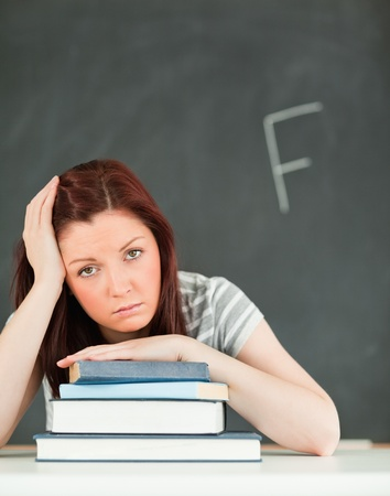 Portrait of a sad young woman receiving a bad mark in a classroom Stock Photo - 10074284