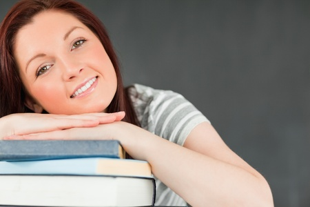 Smiling young student leaned on her books in a classroom photo