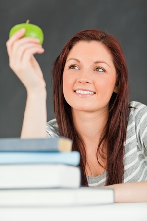 Portrait of a smiling student looking at an apple in a classroom photo