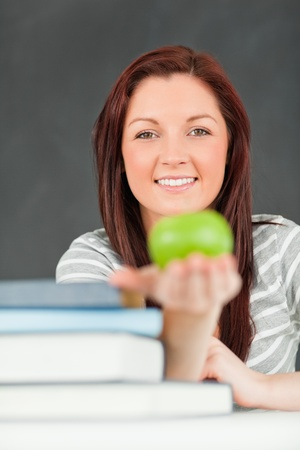 Portrait of a happy student showing an apple in a classroom photo